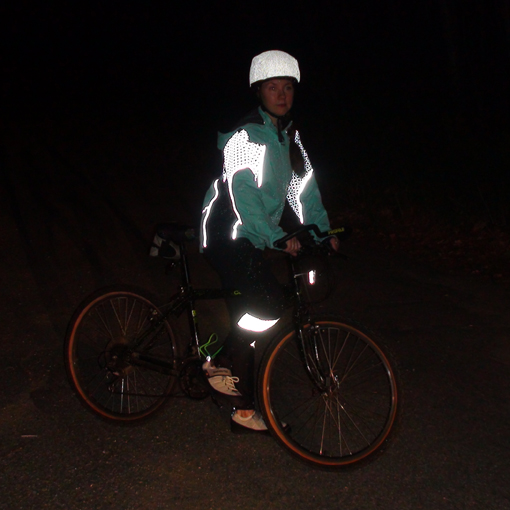 Woman in reflective jacket on a bike at night.